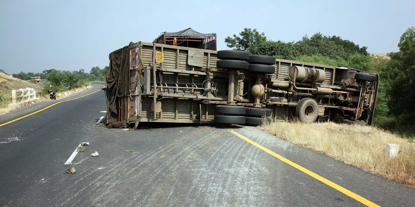 large truck flips on its side and slides off the road