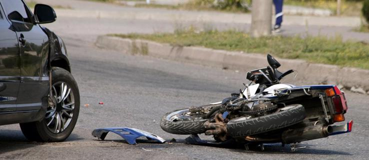 This image shows a motorcycle on the ground after a collision with a car.