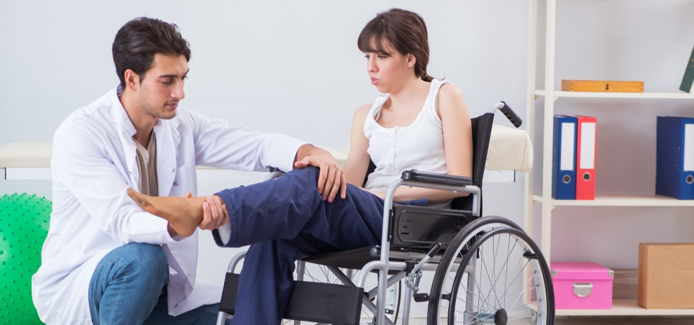 This image shows a woman in a wheelchair being treated by a doctor.
