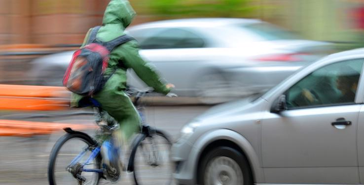 This image shows a bicycle about to be hit by a car as it rains.