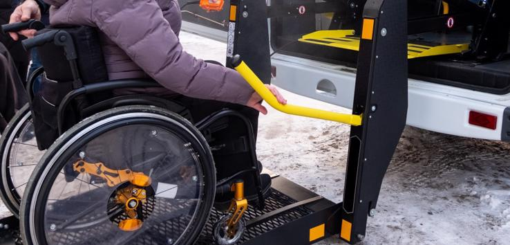 This image shows a woman in a wheelchair being loaded into a taxi with a lift.